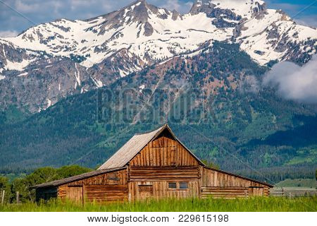 Old mormon barn in Grand Teton Mountains with low clouds. Grand Teton National Park, Wyoming, USA.