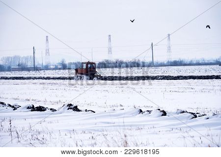 Crawler Tractor Plowing Field In Winter Days.