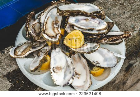 Remains Of Big Fresh Oysters Eaten With Lemon On Plastic Plate Outdoors