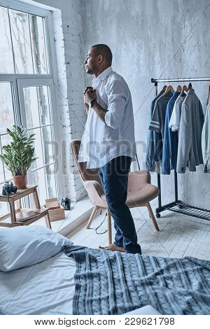 Morning Routine. Handsome Young African Man Putting On Shirt While Standing In The Bedroom At Home