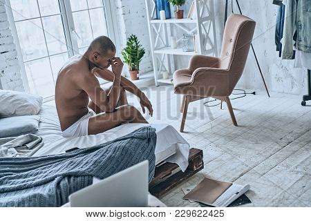Hard To Wake Up. Sleepy Young African Man Massaging Nose While Sitting On The Bed At Home