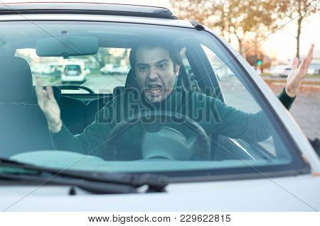 Angry Young Man Driving A Vehicle Is Expressing His Road Rage