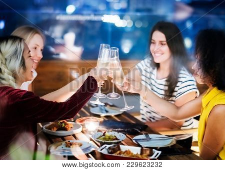 Girl friends toasting at dinner together at a rooftop bar