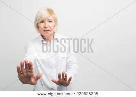 Old And Worried Woman Is Showing That She Is Quite Categorical. She Is Refusal. Cut View. Isolated O