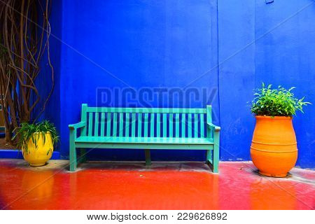 Bench With Plant Pots On The Sides In Colorful Background.majorelle Gardens In Marrakesh (morocco)