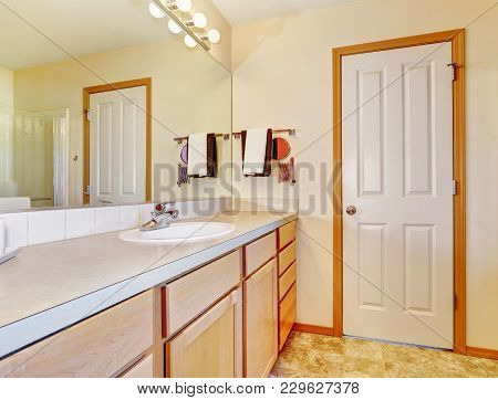 Warm Beige Bathroom With Light Wood Cabinets.