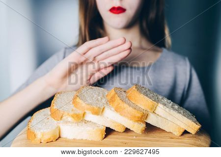 Gluten Intolerance And Diet Concept. Young Girl Refuses To Eat White Bread