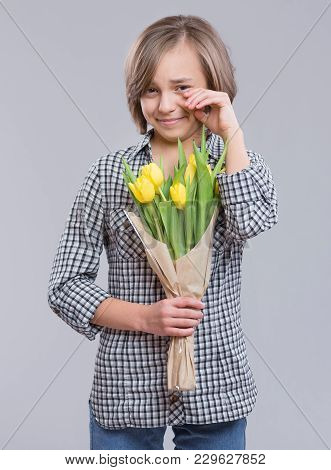 Beautiful Girl With Bunch Of Flowers On Gray Background. Child With Bouquet Of Yellow Tulips As A Gi