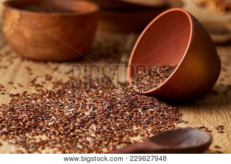 An Overturned Ceramic Clay Bowl With Linseeds On A Brown Rustic Wooden Background Seen From The Open