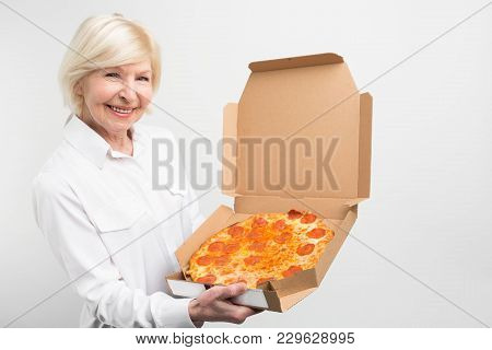 Cut View Of Grandma Holding A Big Box Of Tasty Pizza. She Likes The Junk Food Despice It Is Not Heal