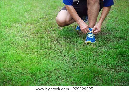 Hands Of Running Or Exercise  Man Tie Blue Sport Shoes Lace On Green Grass Trail Background