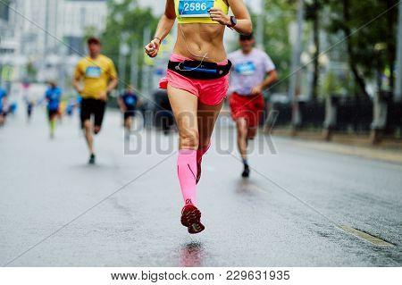 Female Athlete Runner Overtake Group Man Runner In City Marathon