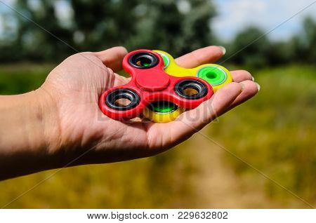 Red And Yellow Fidget Spinners In A Female Hand