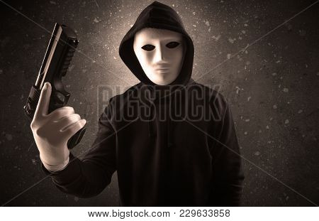 Masked armed villain in empty dark room with gun ax chainsaw mallet wrench