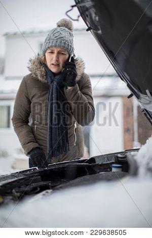 Female Motorist Broken Down In Snow Calling For Roadside Assistance On Mobile Phone