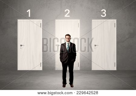 Businessman in grey room with three numbered white  door behind his back
