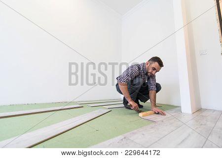 Carpenter Worker Man Installing Wood Parquet Board During Flooring Work With Hammer