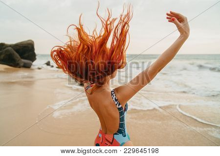 Young Red-haired Woman With Flying Hair On The Ocean Coast At Sunset, Rear View