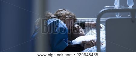 Caring Daughter Hugging Dying Mother With Cancer In The Hospital