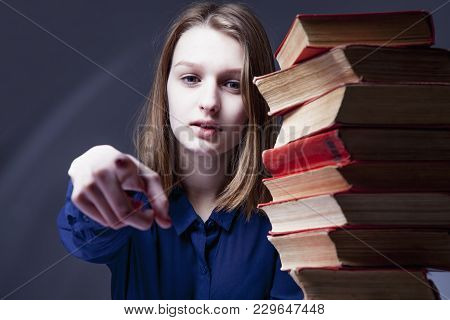 You Have A Chance To Study! Young Woman With Books Pointed At You With The Index Finger. (education