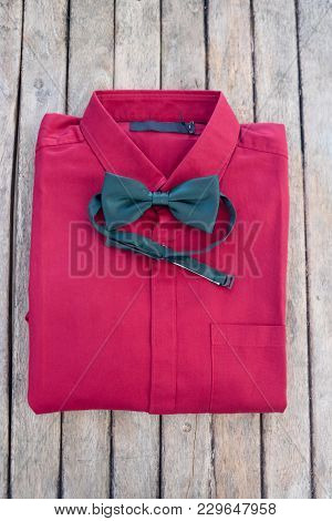 Red Shirt And Green Bow Tie On Wood Table