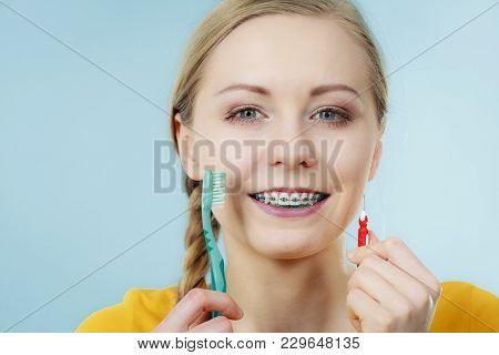 Dentist And Orthodontist Concept. Young Woman With Blue Braces Cleaning And Brushing Teeth Using Two