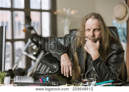 Serious Man In His Office With A Motorcycle