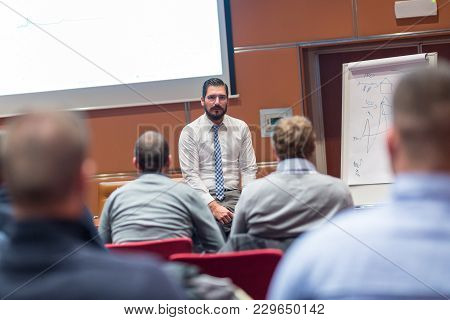 Skilled Coach Asks Questions To Participants Of Informal Company Business Training. Audience In The
