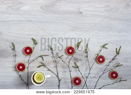 On A Wooden Background Of A Birch Branch With Blossoming Buds Of Green Buds And A Red Biscuit A Cup