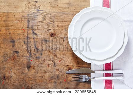 Empty Plate With Cutlery On A Wooden Background. Space For Writing Or Placing Text Menu