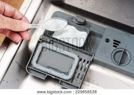 Hand Is Pouring White Washing Powder Into A Dishwasher To Clean Dirty Dishes