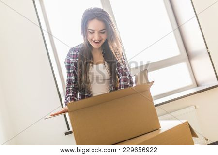 Woman Packing And Unpacking In A Carton Box When Moving Home