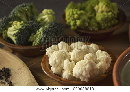 Fresh Pieces Of Cauliflower, Broccoli And Romanesco Broccoli In Small Rustic Wooden Bowls. Selective