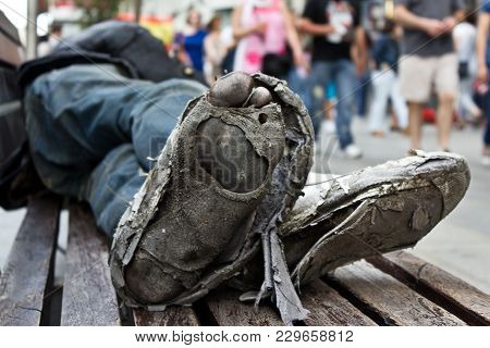 Homeless Man´s Sleeping In A Bench With Rotten And Dirty Feet Crossed With Destroyed Shoes From A Lo