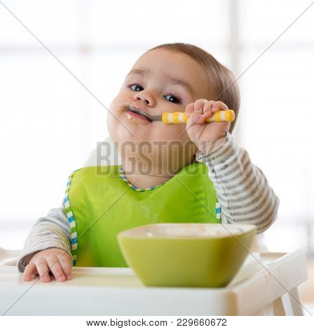 Baby Child Eats Healthy Food Himself With Spoon. Portrait Of Happy Kid Boy In High Chair.