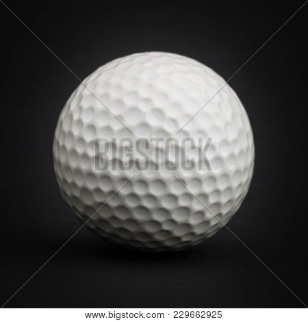 White Golf Ball Isolated On Black Background On A Studio Shot.