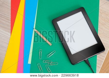 Ebook Device Charging On A Table With Colour Paper Sheets, A Pencil And Some Paperclips. Creative Le