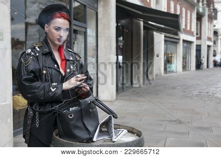 London, Uk - August 27, 2016:  Girl With Red Hair Dressed In A Militaristic Style Of Smokes On The S