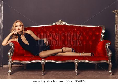 Fashionable Young Woman In A Black Evening Dress Lies On A Red Antique Couch