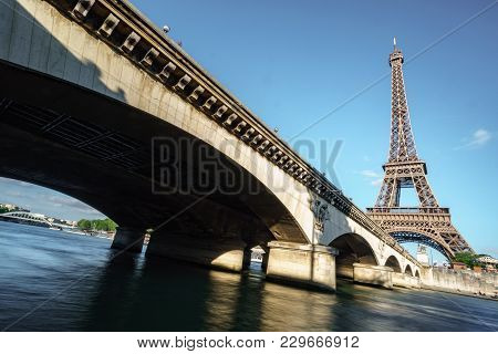 Wide Angle Bottom View Of The Eiffel Tower, Bridge And Seine River, Long Exposure In Paris, France
