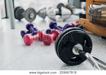 Set Of Equipment For Weightlifting And Fitness: Dumbbells, Barbell And Rowing Machine At Gym.