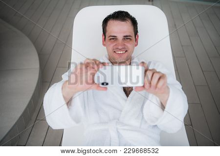 A Man In A White Bath Robe Lies By The Pool On A Deck Chair And Looks Into The New Expensive Mobile