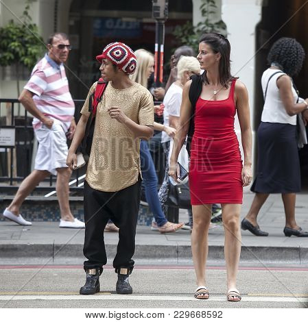 London, Uk - August 27, 2016: A Man In A Rastafarian Hat And A Woman In A Red Dress At A Traffic Lig