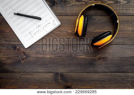 Work Desk Of Modern Composer. Music Notes Near Headphones On Dark Wooden Background Top View.
