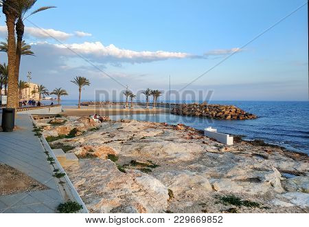 Torrevieja, Spain - February 17,  2018: People Walking By The Seafront Of Torrevieja At Sunset. Cost