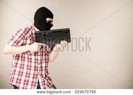 Crazy Hacker Man. Unrecognizable Guy Wearing Black Balaclava Holding Computer Keyboard. Hate Speech