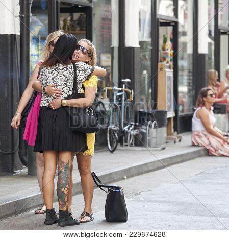 London, England - July 12, 2016 Three Girls In Short Dresses Met On The Street And Hugging
