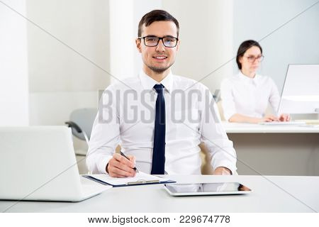Young businessman in office smiling looking at camera