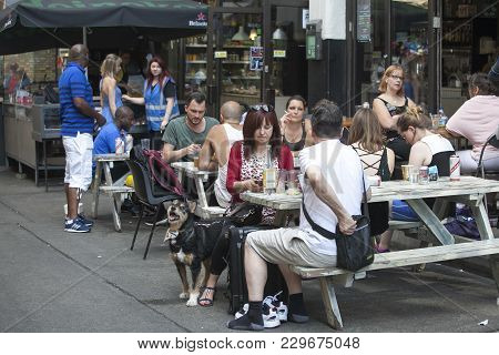 London, England - July 12, 2016 The Girl With A Dog And A Suitcase Sitting In A Street Cafe