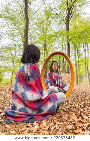 Colombian Woman Sitting In Beech Forest With Mirror During Spring